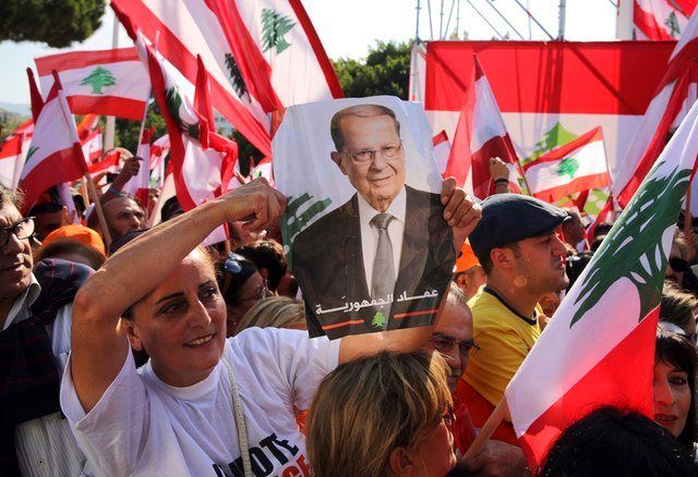 A Lebanese woman holds a picture of newly elected president Michel Aoun in Baabda, east of Beirut, Nov. 6, 2016.