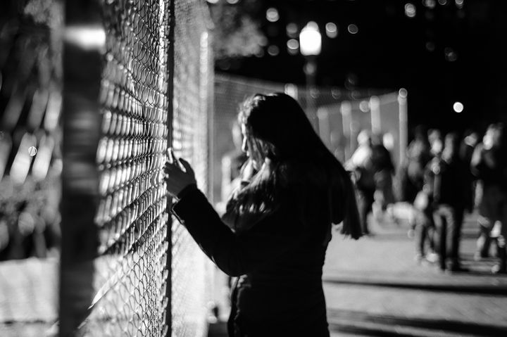 <em>A woman texts and clutches the fence separating the White House and Lafayette Park on election night.</em>