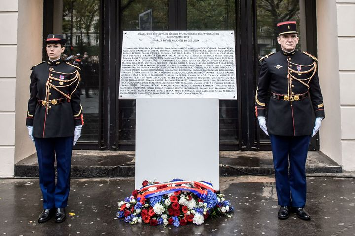 """French Republican Guards stand next to a commemorative plaque reading """"In memory of the injured and killed victims of the attacks of November 13, 2015 - to the 90 lives taken"""" at the Bataclan concert hall in Paris."""