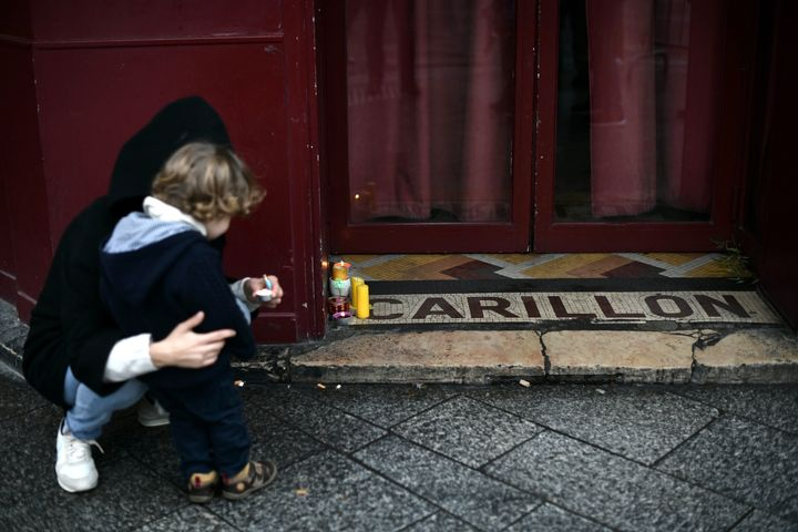A woman with her child lays candles in tribute to the victims, outside Le Carillon restaurant near Rue Alibert and Rue Bichat in Paris.