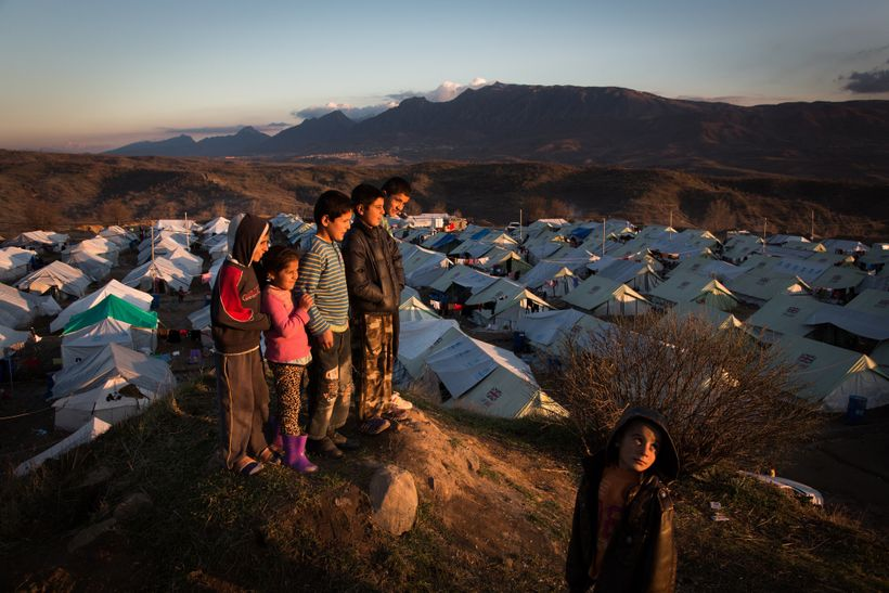 Children look out at the sunset over the Bamarne IDP camp in northern Iraq