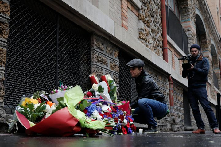 "A woman pays her respects under a commemorative plaque next to the ""La Belle Equipe"" bar and restaurant, in Paris, France, No"