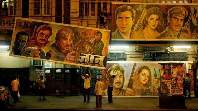 Sheik Rehman and his crew changing billboards in front of the Alfred Talkies movie theatre in a scene from <em><strong>Origin