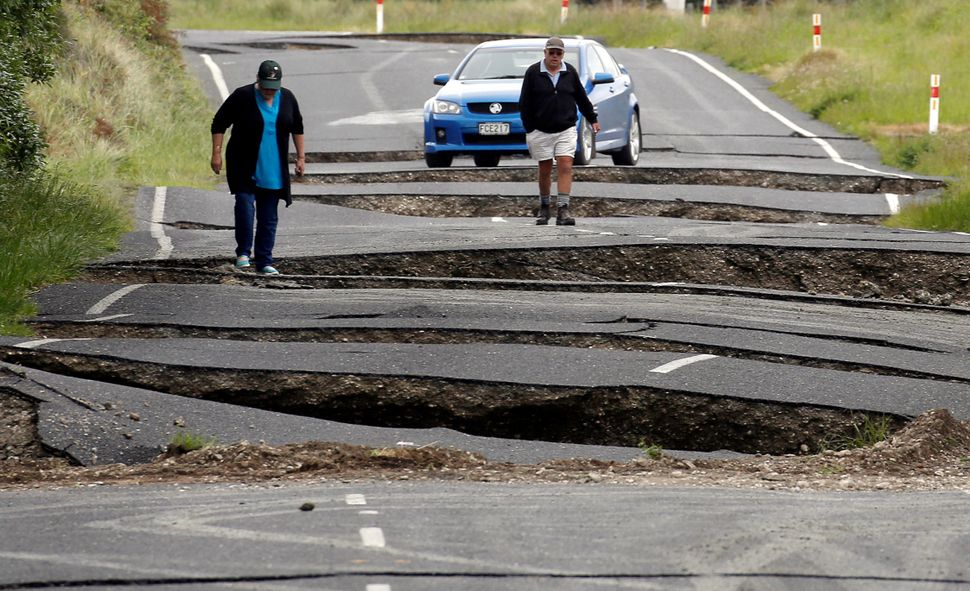 Local residents Chris and Viv Young look at damage caused by an earthquake, along State Highway One near the town of Ward, on
