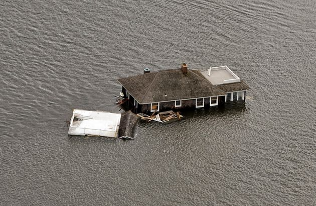 This photograph shows a house floating in the bay after it was washed from its foundation in Manotoloking,...