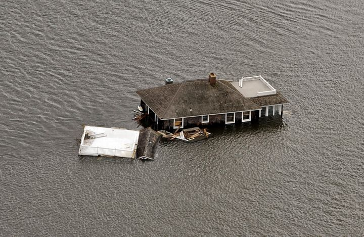 This photograph shows a house floating in the bay after it was washed from its foundation in Manotoloking, New Jersey, d