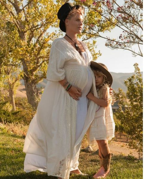 Pink Cradles Baby Bump In Adorable Pregnancy