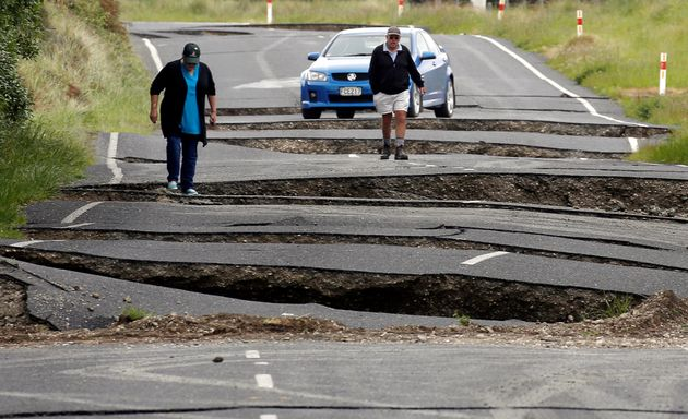 Locals inspect the damage to a roadsouth of Blenheim on New Zealand's South