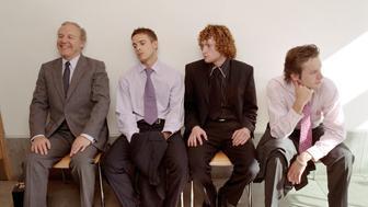 Four businessmen waiting in foyer