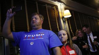 A man wearing a shirt in support of Donald Trump, 2016 Republican presidential nominee, holds a mobile device during a U.S. presidential election night watch party thrown by Butler County For Trump in West Chester, Ohio, U.S., on Tuesday, Nov. 8, 2016. Fifty-one percent of voters nationally were bothered a lot by Republican Donald Trump's treatment of women, while Democrat Hillary Clinton's use of private e-mail while secretary of state was troubling to 44 percent, according to preliminary exit polling as voting neared a close in some states. Photographer: Luke Sharrett/Bloomberg via Getty Images