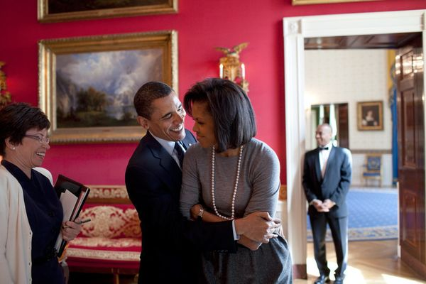 President Barack Obama hugs first lady Michelle Obama in the Red Room while senior advisor Valerie Jarrett smiles at the