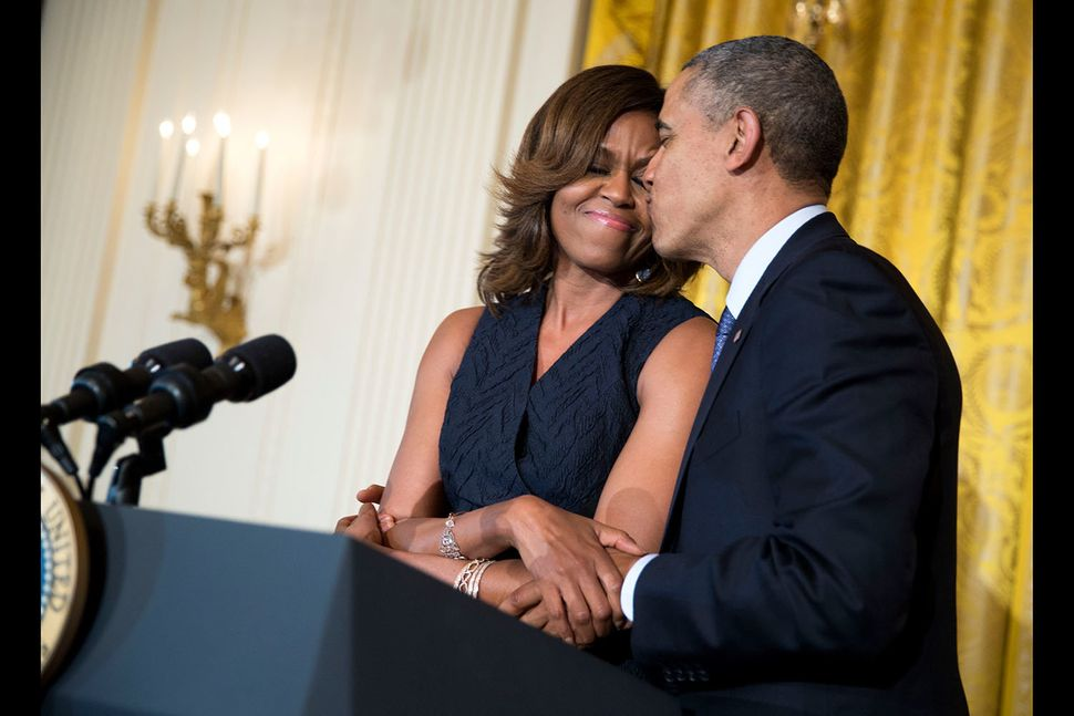 President Barack Obama kisses first lady Michelle Obama during her remarks at an Affordable Care Act reception in the East Ro