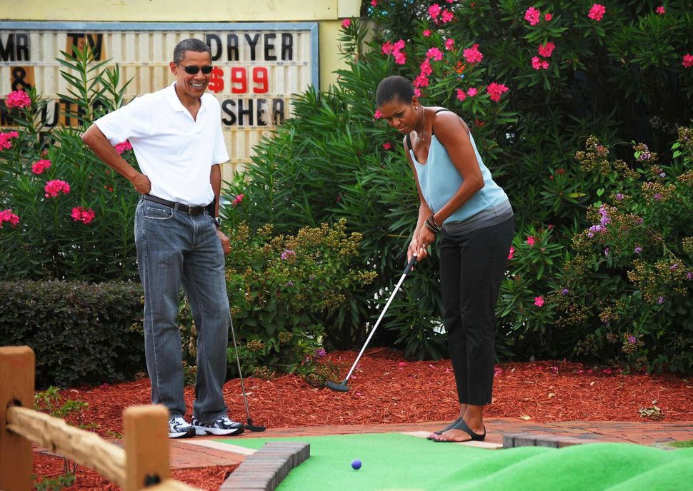President Barack Obama watches as first lady Michelle Obama putts during a round of mini golf at Pirate's Island Golf on Aug.