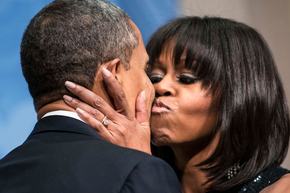 President Barack Obama is kissed by first lady Michelle Obama during an inauguration reception at the National Building Museu