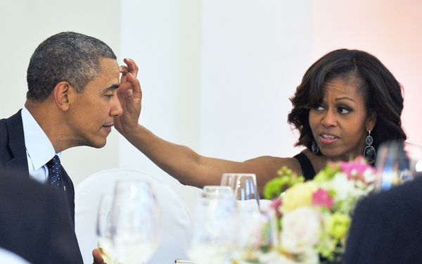 First lady Michelle Obama wipes something from President Obama's forehead during a dinner at the Schloss Charlottenburg Palac