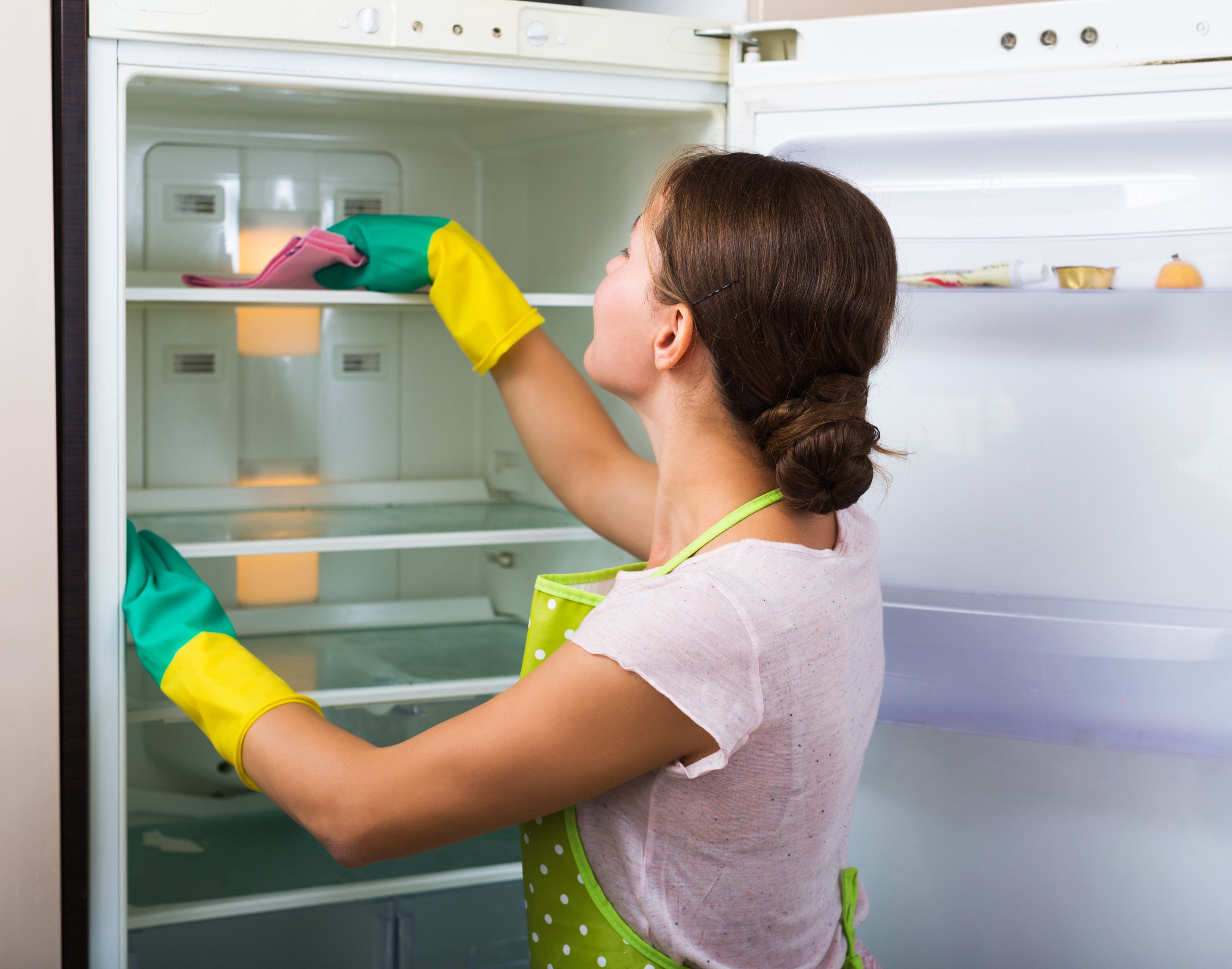 Adult housewife cleaning refrigerator inside and smiling