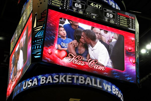 President Barack Obama and first lady Michelle Obama are shown kissing on the kiss cam screen during a timeout in the Olympic
