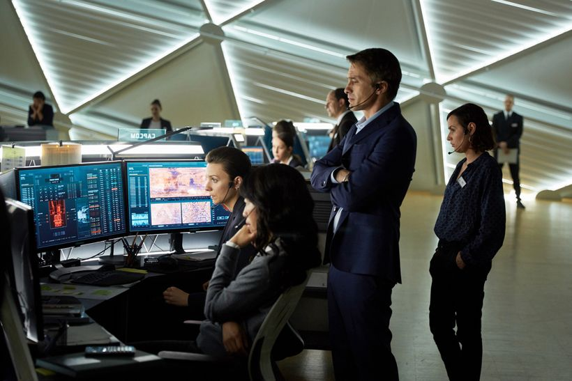 Olivier Martinez as Ed Grann the French CEO of the Mars Mission Corporation looks on over Jihae as Joon Seung the Korean-Amer