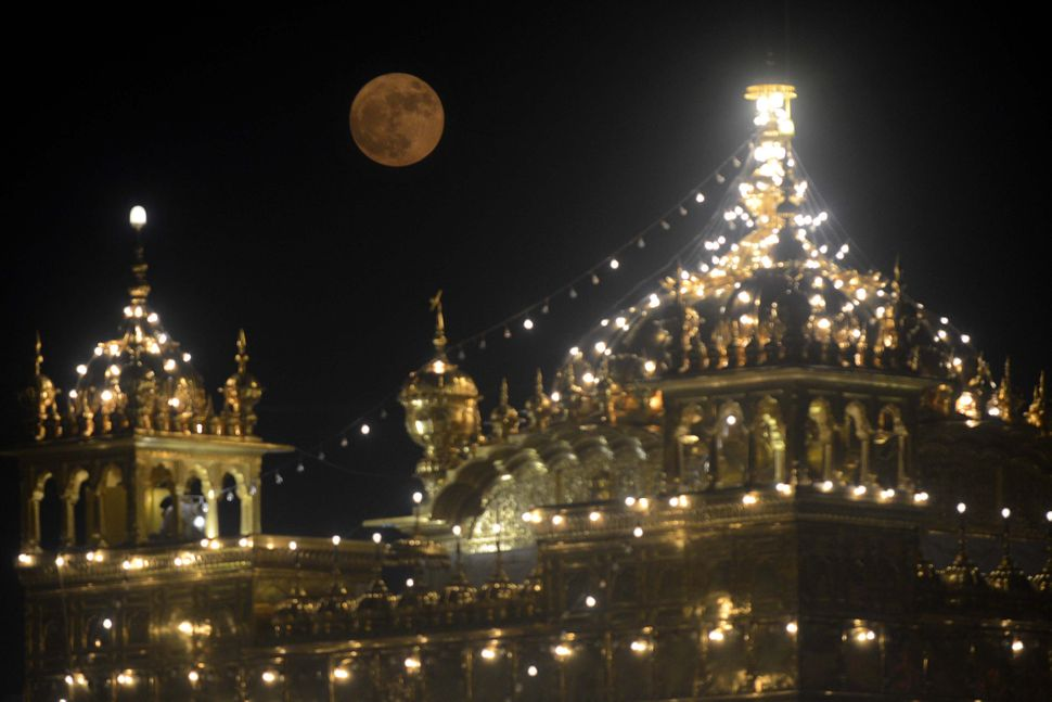 "The ""supermoon"" rises over the Sikh Shrine, the Golden Temple in Amritsar, on Monday."