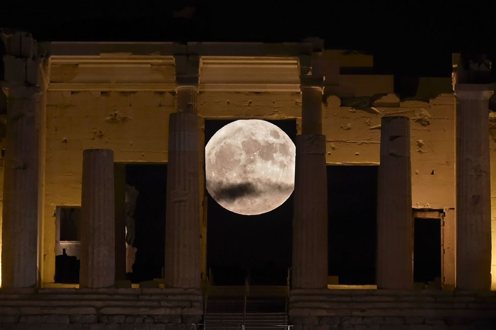 "The ""supermoon"" rises on Monday behind the Propylaea above the Ancient Acropolis hill in Athens."