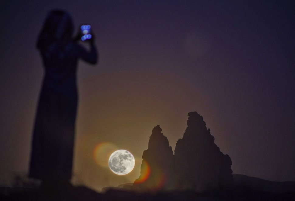 "A woman takes a picture as a ""supermoon"" rises on Monday over the desert near Tabuk, some 1,500 kilometers away from the Saud"