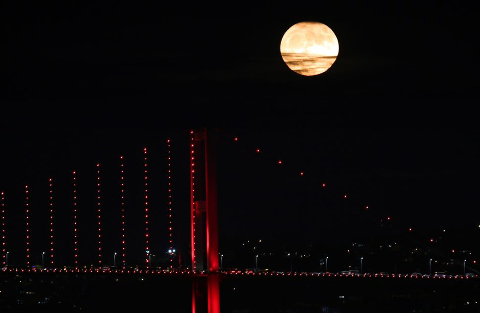 "The ""supermoon"" rises over Martyrs' Bridge in Istanbul on Monday."
