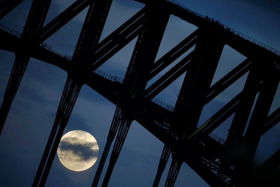 Participants in a Sydney Harbour Bridge Climb walk down the western span of the famous Australian landmark as the supermoon r