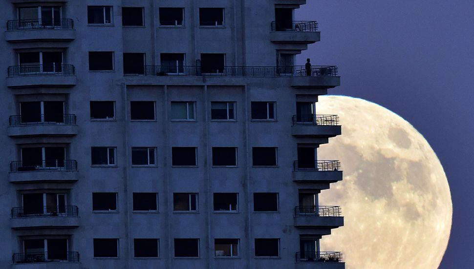 "A man stands on a balcony in Madrid on Sunday, the eve of a ""supermoon,"" as the moon rises in background."