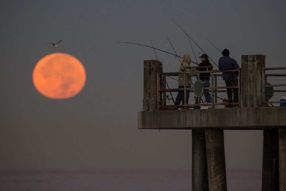 The moon sets behind people fishing on a pier in Redondo Beach, California.