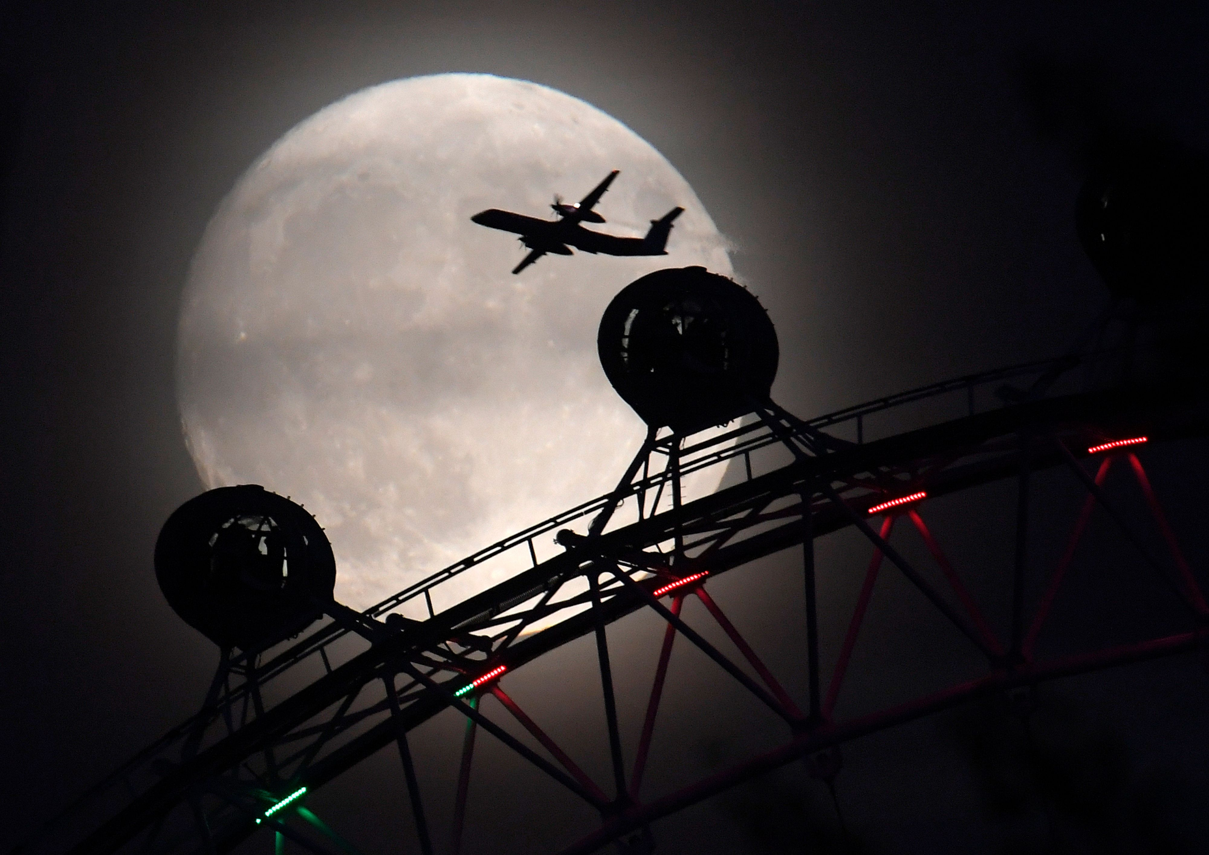"An airplane flies past the London Eye on Sunday, one day before the ""supermoon"" spectacle."