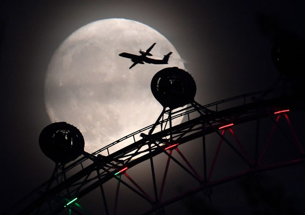"""An airplaneflies past the London Eye on Sunday, oneday before the """"supermoon"""" spectacle."""