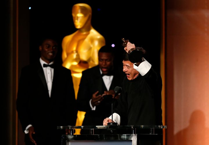 Chris Tucker looks on as Jackie Chan accepts his award.
