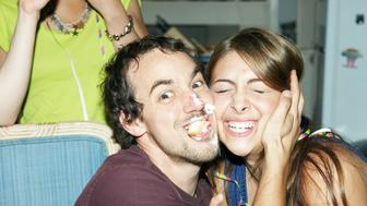 Man with cake on his face hugging friend
