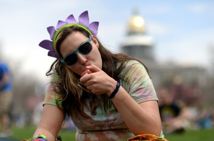 A young womansmokes marijuana during the 420 Rally weekend at theCivic Center Park in Denver, Colorado on April 1