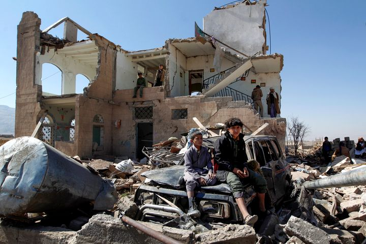 Children sit amidst the rubble of a house hit by Saudi-led coalition air strikes two days earlier on the outskirts of the Yem