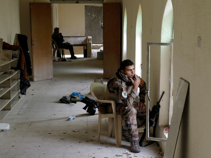An Iraqi special forces soldier smokes while seated in his position inside a mosque in Mosul, Iraq, November 15, 2016.
