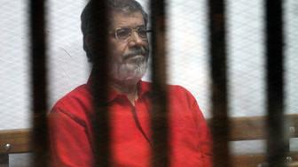 CAIRO, EGYPT - JUNE 18: Egypts ousted President Mohamed Morsi is seen behind the bars during his trial on charges of espionage on behalf of Qatar at the Police Academy in Cairo, Egypt on June 18, 2016.  (Photo by Ahmed Gamil/Anadolu Agency/Getty Images)