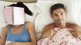 Bored Looking Man Lying In Bed Next To Woman Reading Book Looking At Camera Frustrated