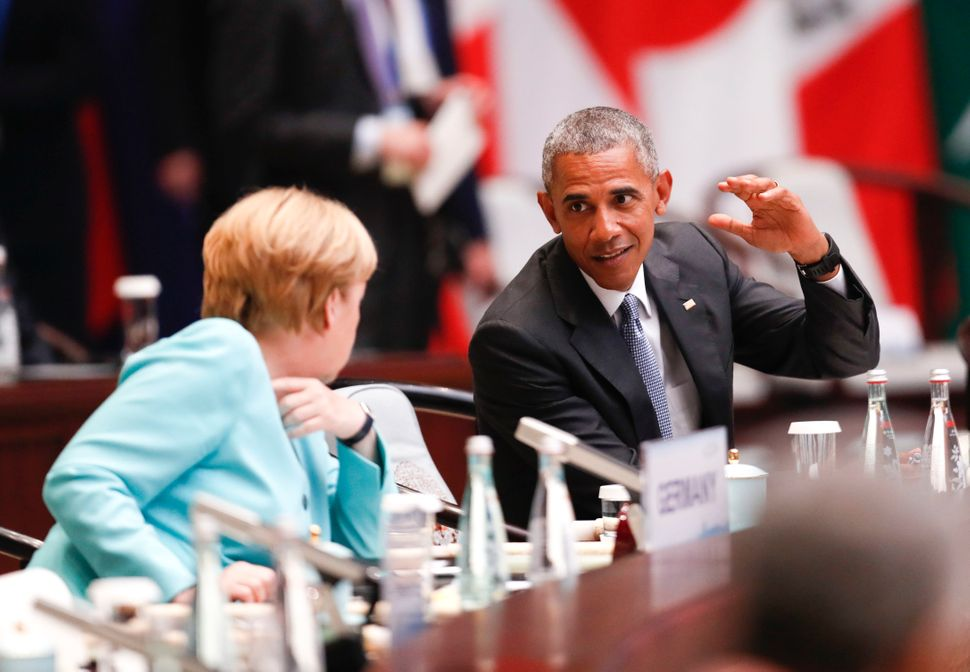 Merkel speaks with Obama during the opening ceremony of the G20 Leaders Summit at the Hangzhou International Expo Center on S