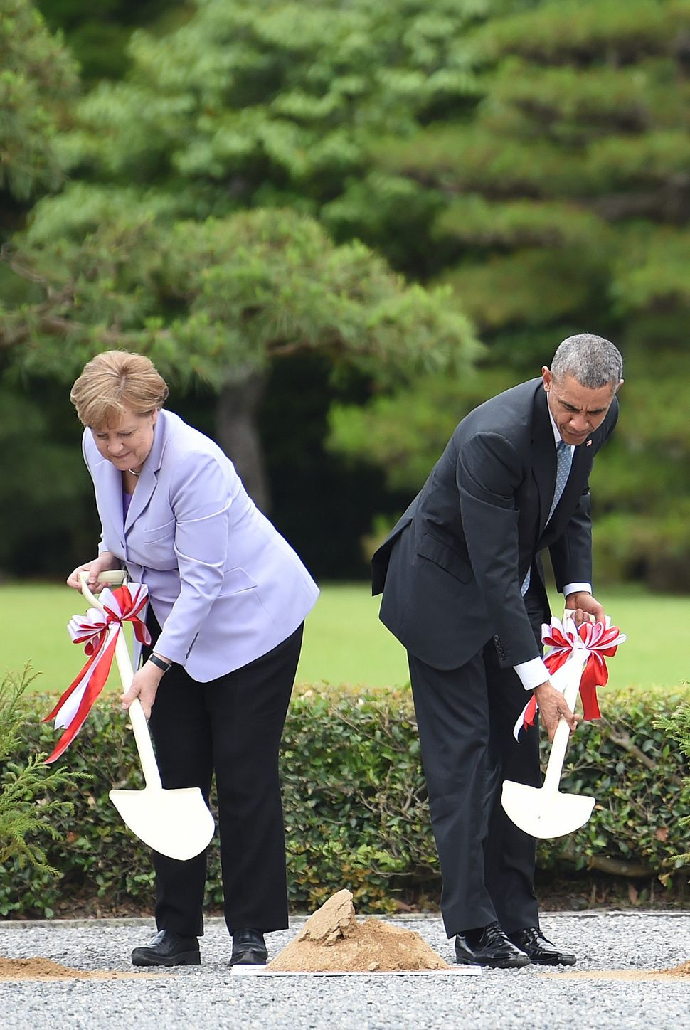 Merkel and Obama take part in a tree-planting ceremony on the grounds of the Ise-Jingu Shrine in the city of Ise, in Mie pref