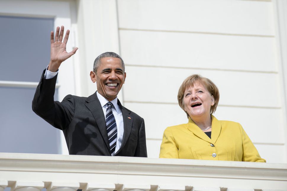 Obama waves during a welcome ceremony at Herrenhausen Palace accompanied by Merkel on Obama's first day of a two-day trip to