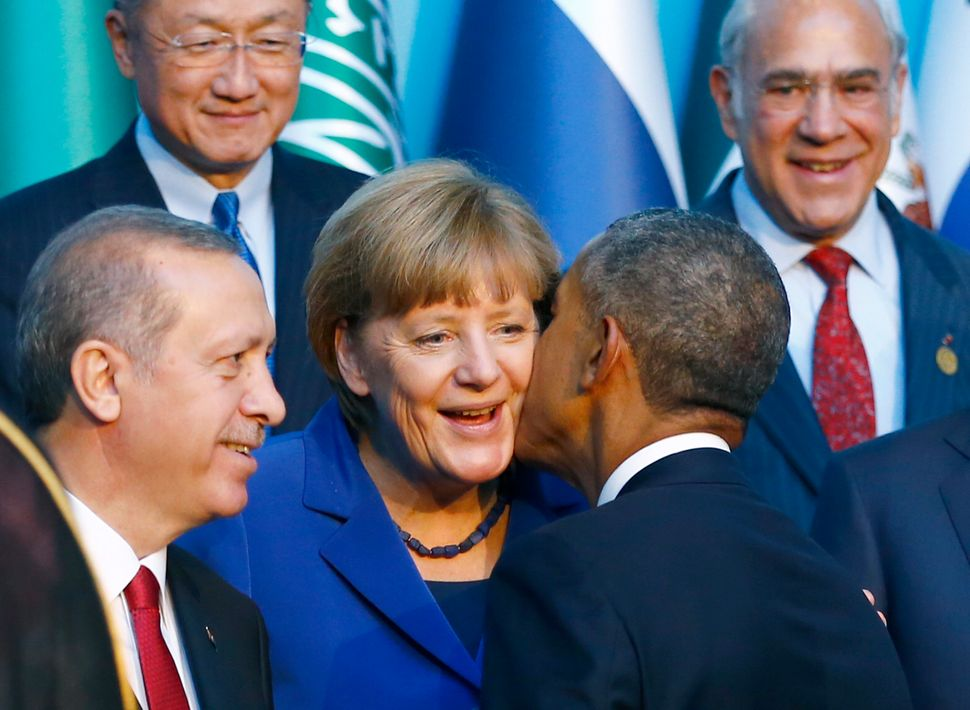 U.S. President Barack Obama kisses German Chancellor Angela Merkel as members of the Group of 20 prepare for the traditional