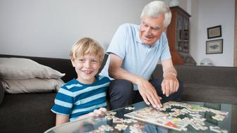 Portrait of happy grandson solving jigsaw puzzle with grandfather in living room at home