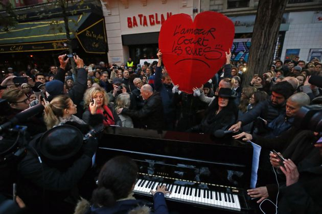 People pay their respects to those killed at the Bataclan concert hall in Paris a year after the
