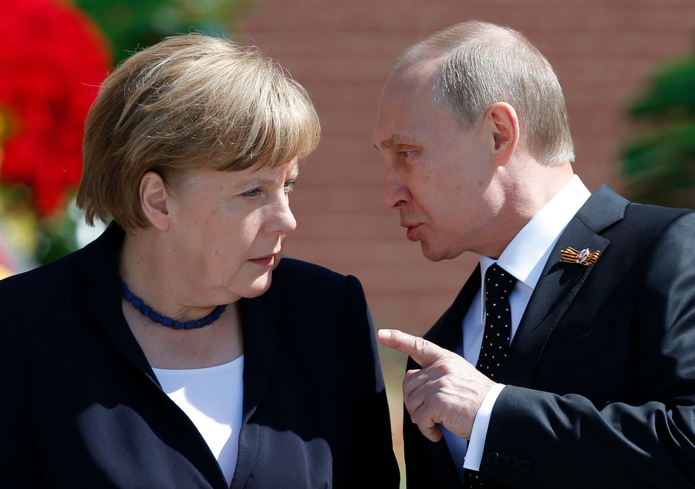 Russian President Vladimir Putin speaking with German Chancellor Angela Merkel at the Tomb of the Unknown Soldier by the Krem