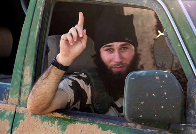 An Islamic State fighter gestures from a vehicle in the countryside of the Syrian Kurdish town of Kobani,...
