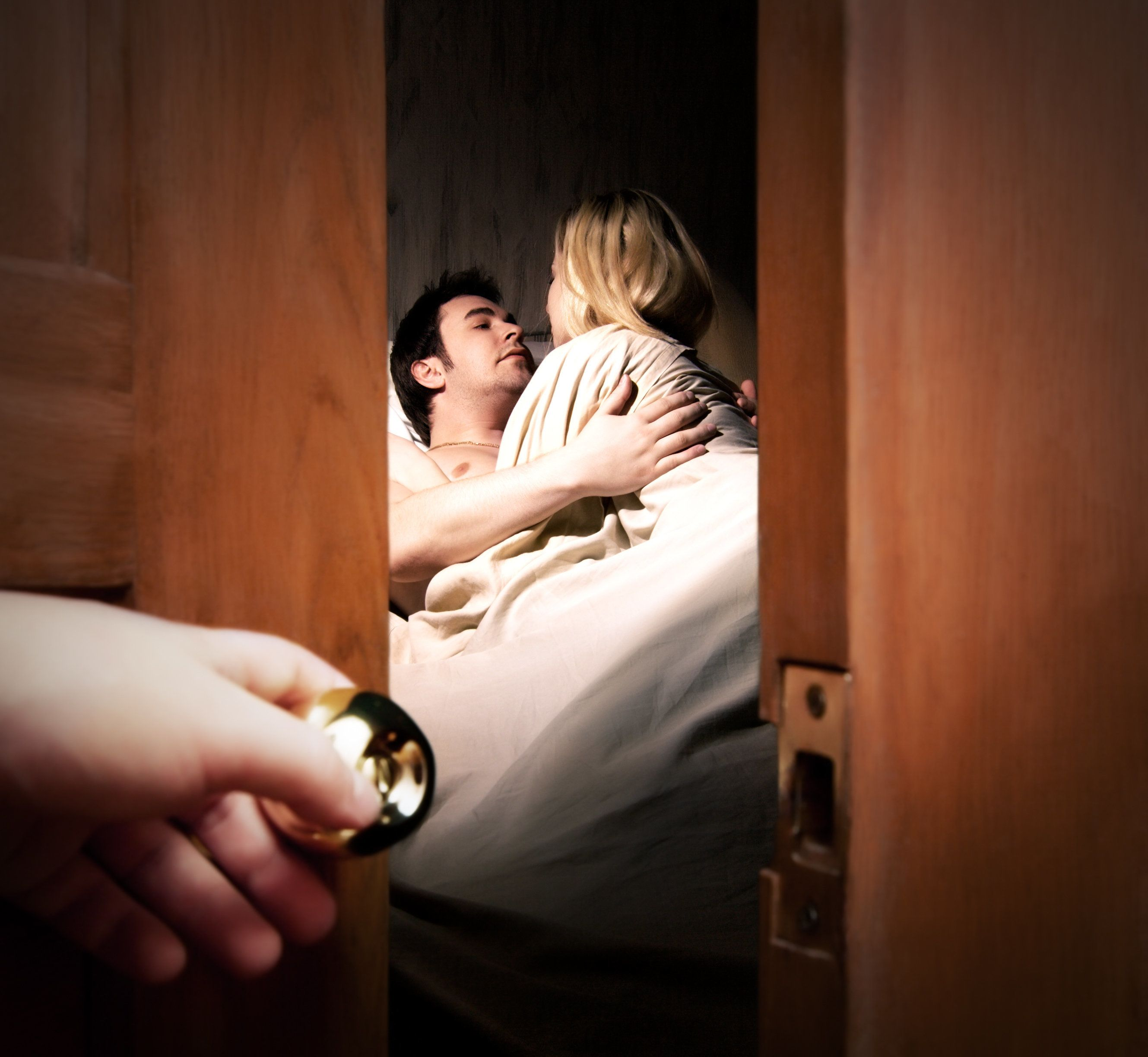 Couple lying in bed while someone is watching in front of the door