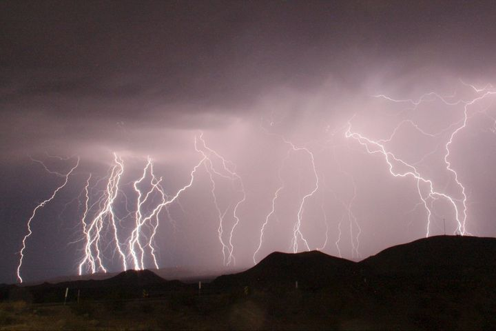 A long-exposure photograph shows lightning bolts illuminating the night sky north of Barstow, California, in 2015.