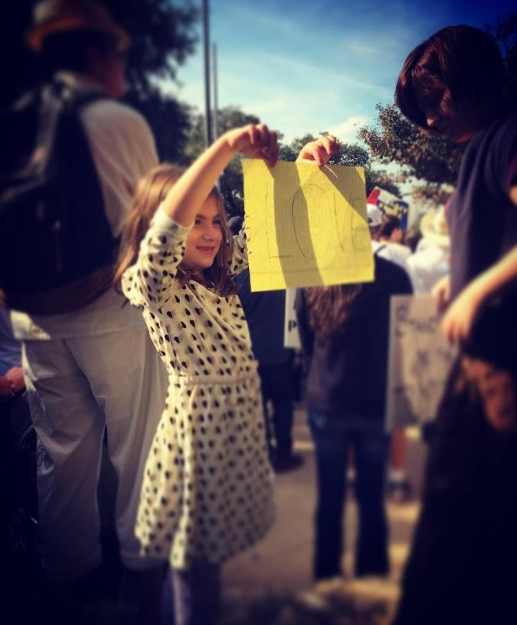 Daughter holding up a sign at a peaceful gathering in Austin.