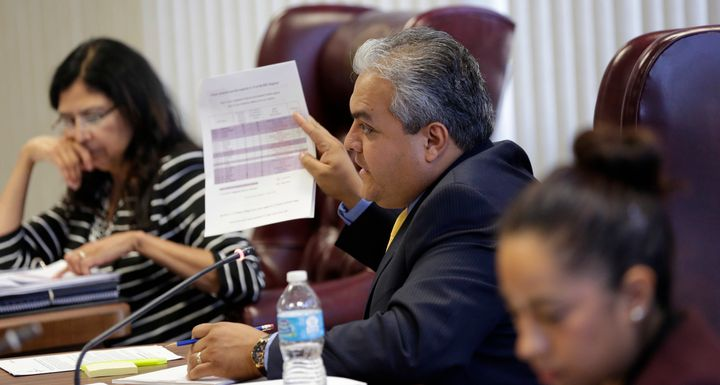 State Board of Education member Ruben Cortez Jr., center, questions a speaker during a hearing, April 8, 2014, in Austin, Tex